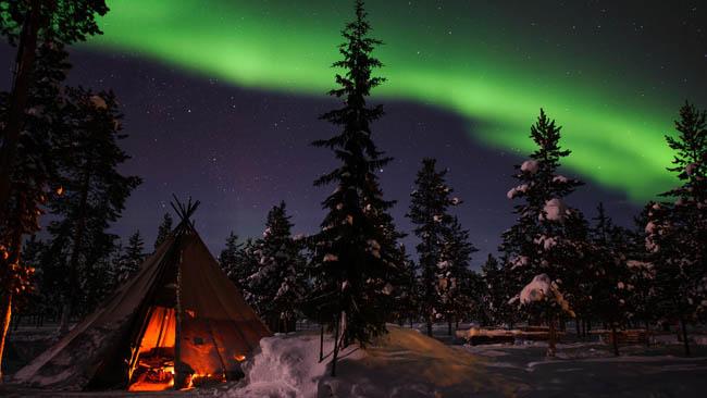 Northern Lights above tents at the reindeer lodge in Jukkasjärv